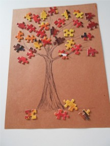 A picture of a puzzle leaf tree. The trunk and branches are drawn and the puzzle pieces are painted orange, red, and yellow and used as leaves.