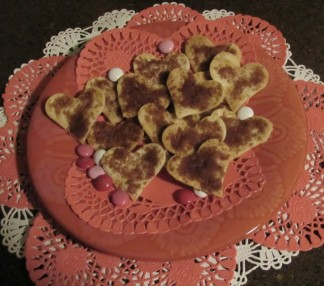 Heart shaped baked tortilla treats with cinnamon on top. On top of heart shaped paper doilies.