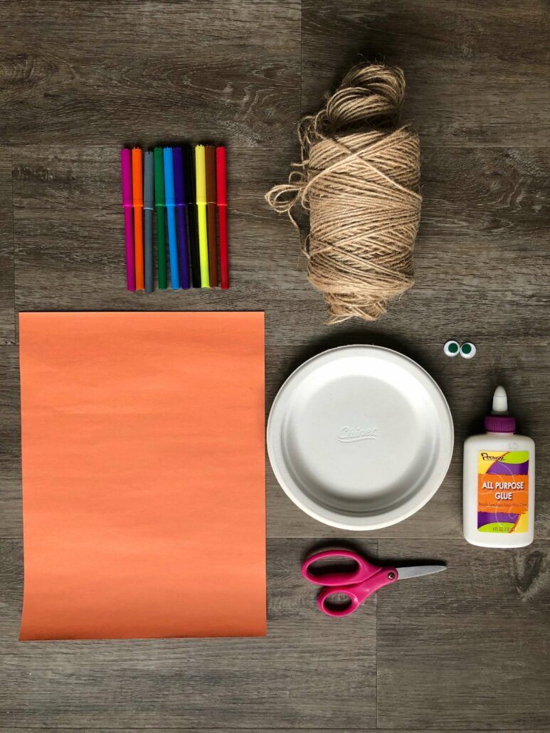 An image of all the materials used to make the paper plate face craft: markers, twine string, orange construction paper, paper plate, googly eyes, glue, and scissors.