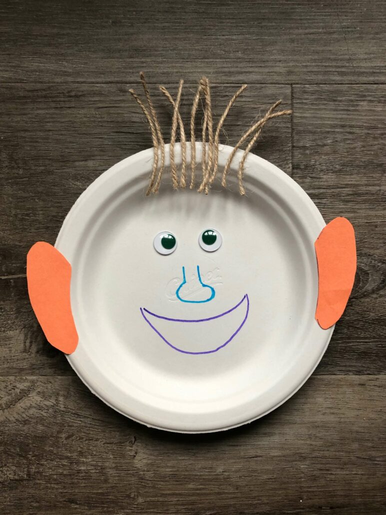 An image of the finished paper plate face craft. The paper plate has a purple mouth, blue nose, googly eyes, orange construction paper ears, and twine hair.